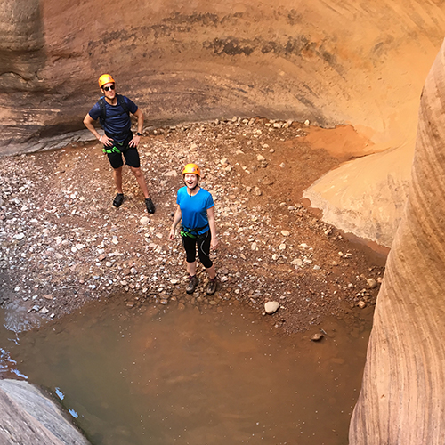 two people standing in a canyon in shallow water