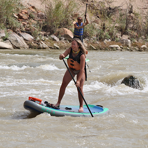 woman on a paddle board paddling through a rapid