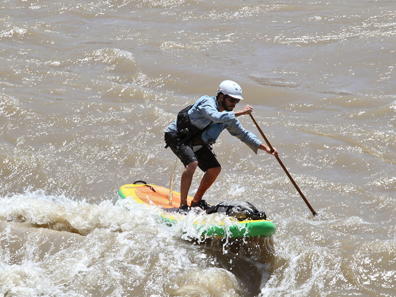 person paddling through a strong rapid