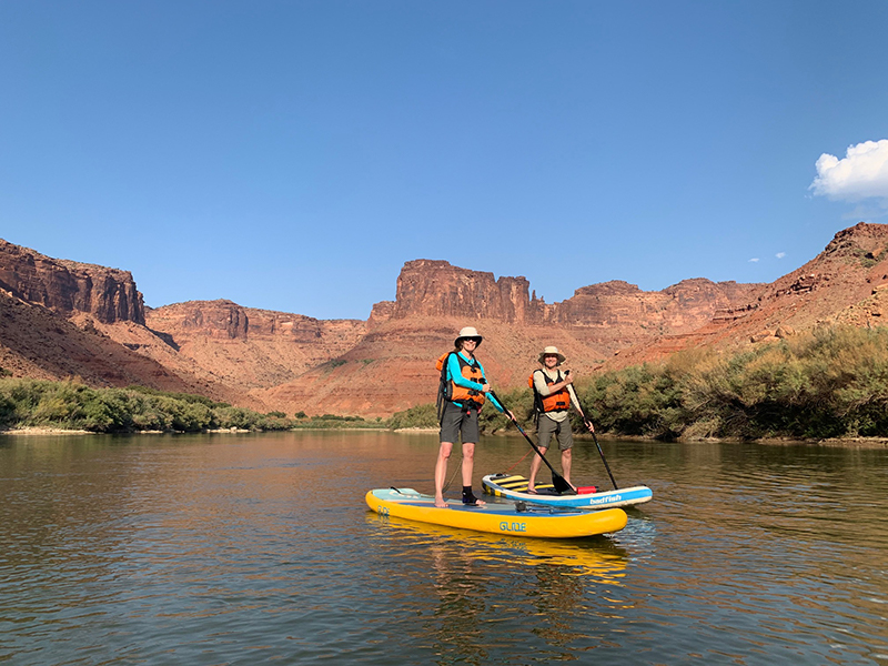 people standing on paddle boards with desert views behind them