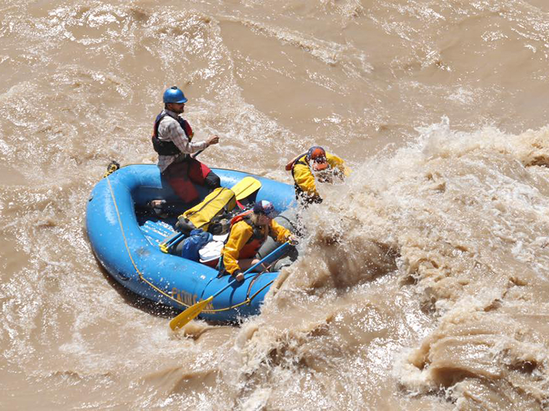 people in a raft hitting a large wave