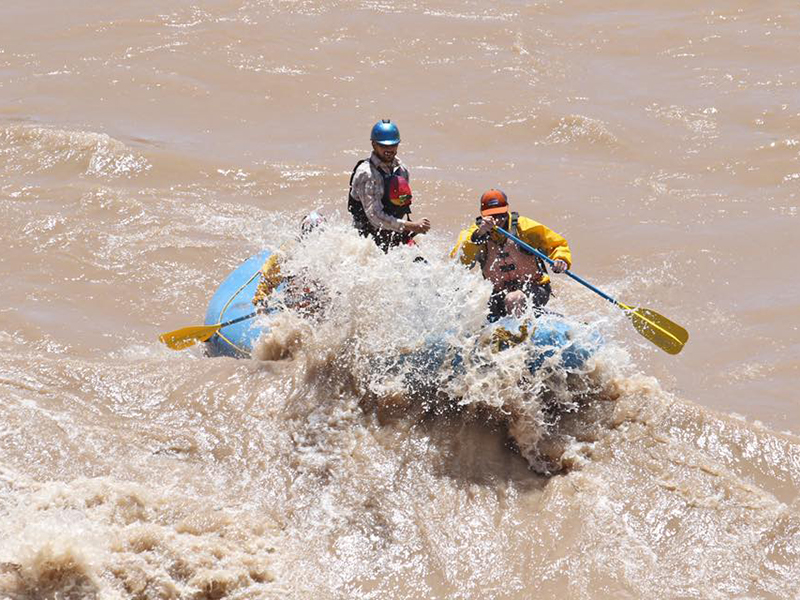 people in a raft paddling through a rapid