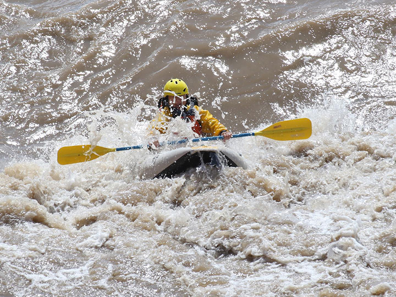 person in a kayak hitting a large rapid