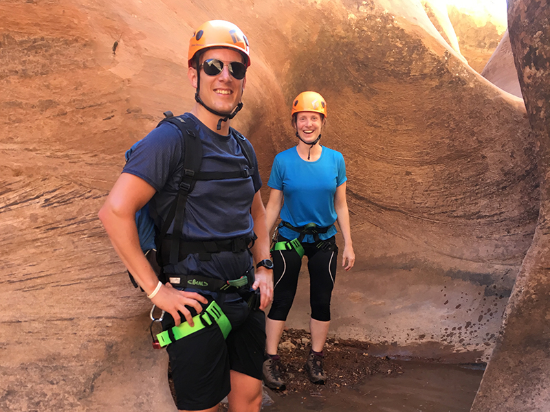 two people smiling in a canyon standing in shallow water