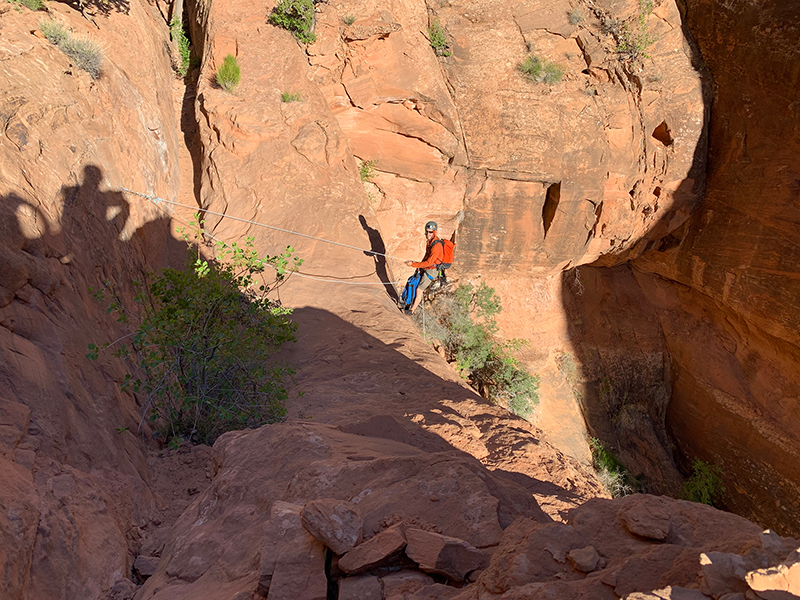 person rappelling into a canyon