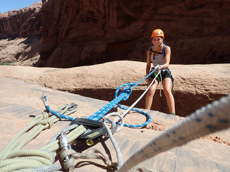 woman in helmet at the top of a canyon