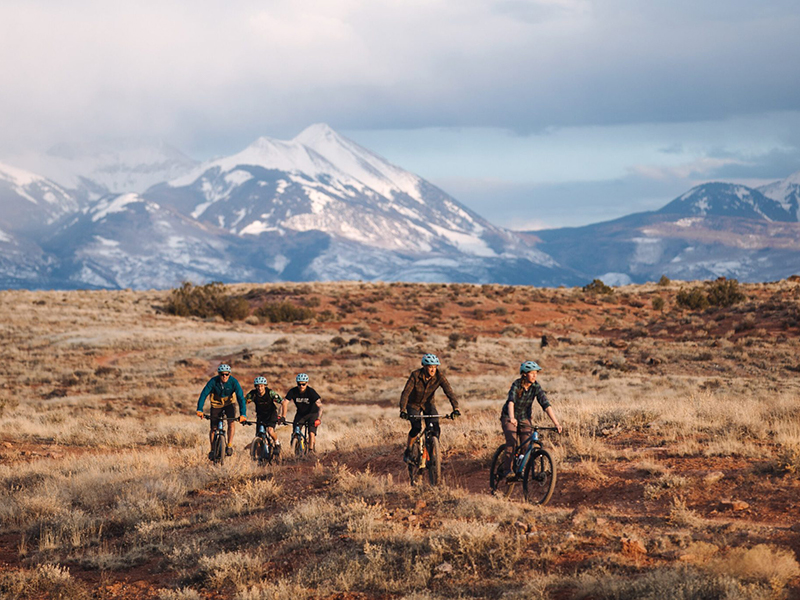 group of people on bikes with mountains in background