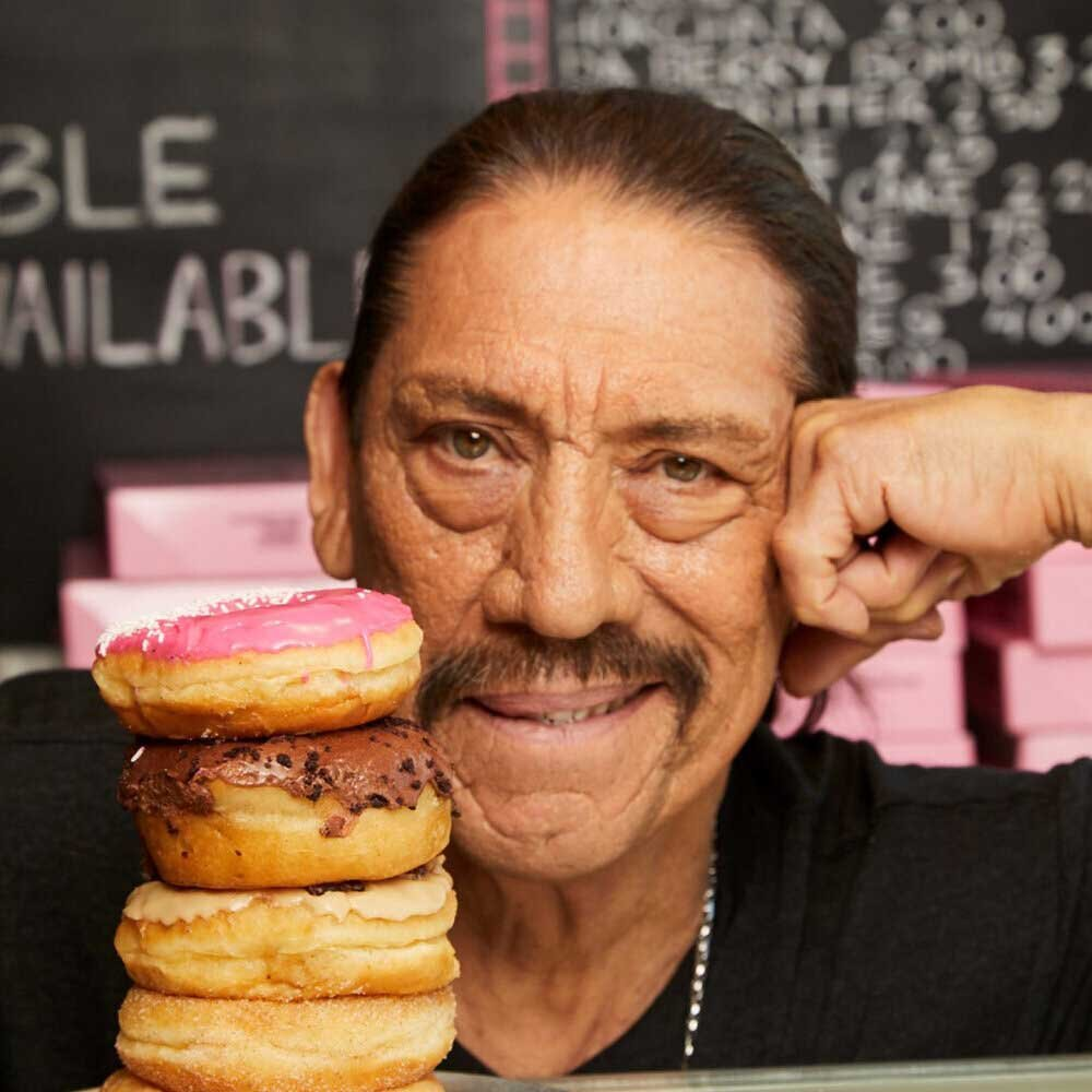 Danny Trejo with a stack of donuts at Trejo's Coffee & Donuts
