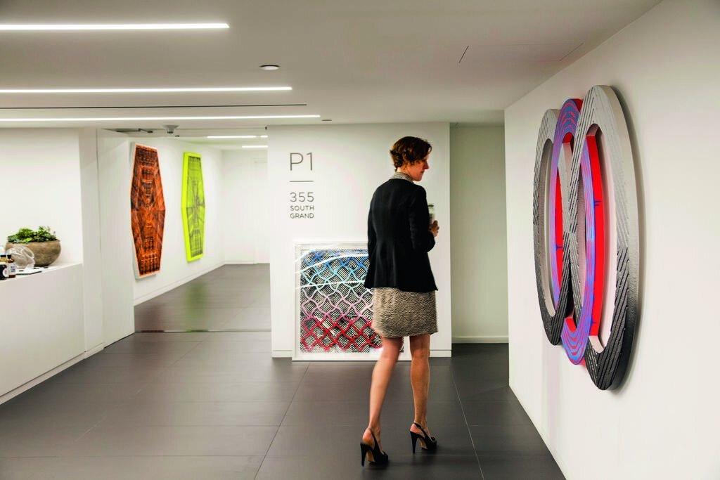 Woman standing in Underground Art Series gallery featuring artist Jason Revok at Wells Fargo Center parking lobbies