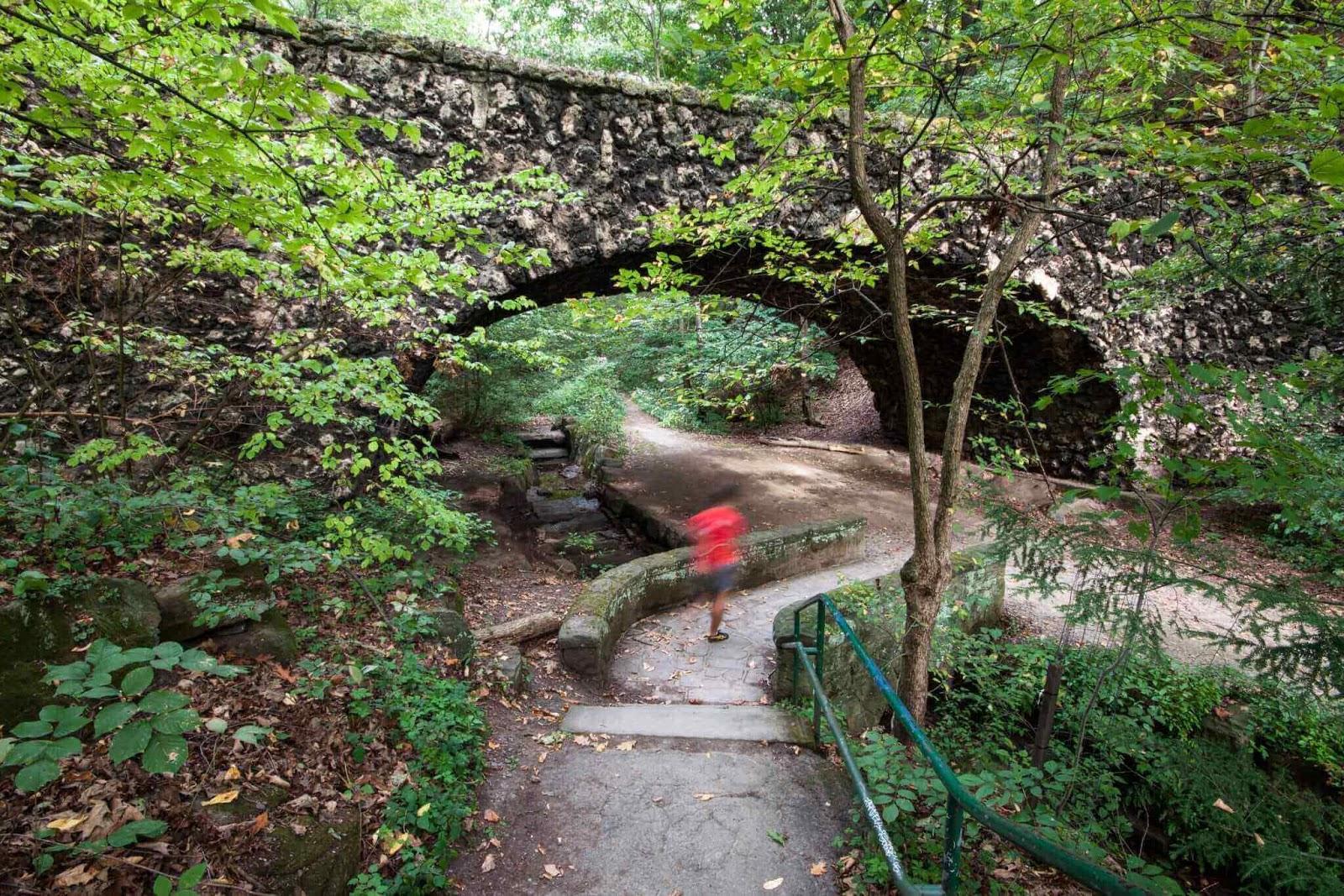 Man walking under stone bridge in park