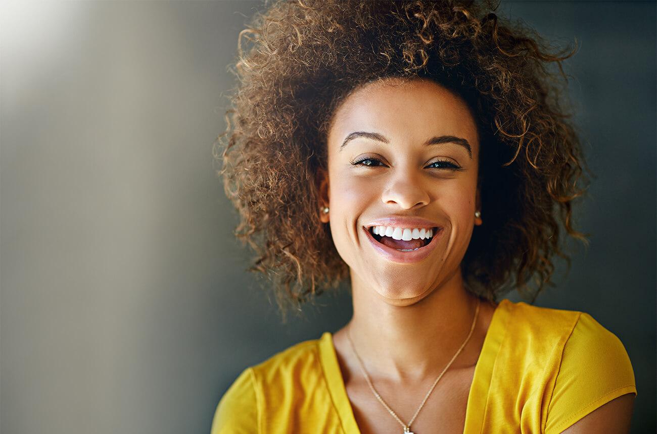 Eine Frau mit gelben T-Shirt lächelt freundlich.