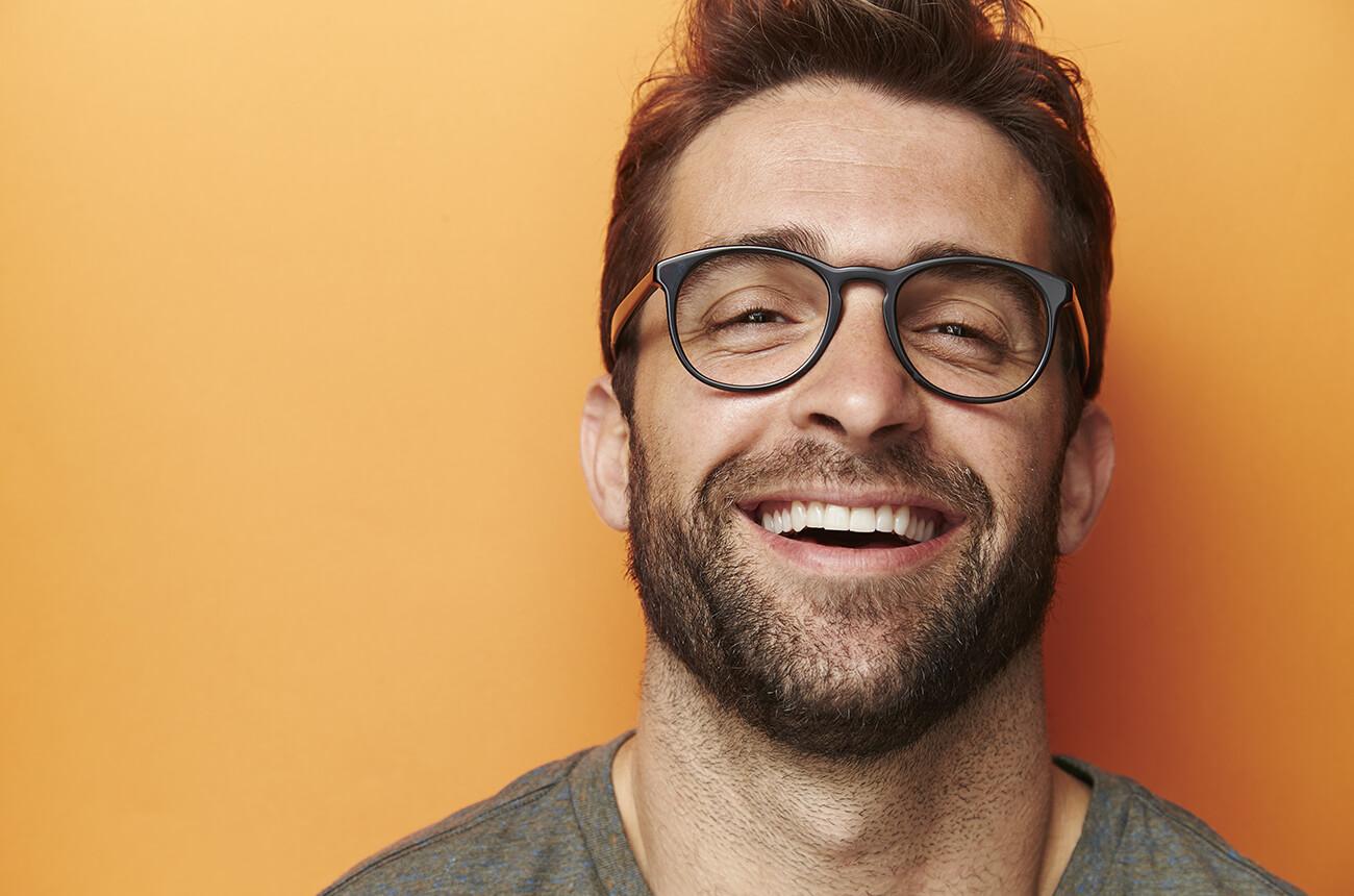 Ein junger Mann mit braunen Haaren, Stoppelbart und Brille lächelt.