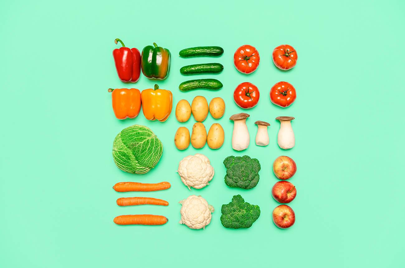 Verschiedenes Gemüse ordentlich aufgereiht auf einem hellgrünen Hintergrund.