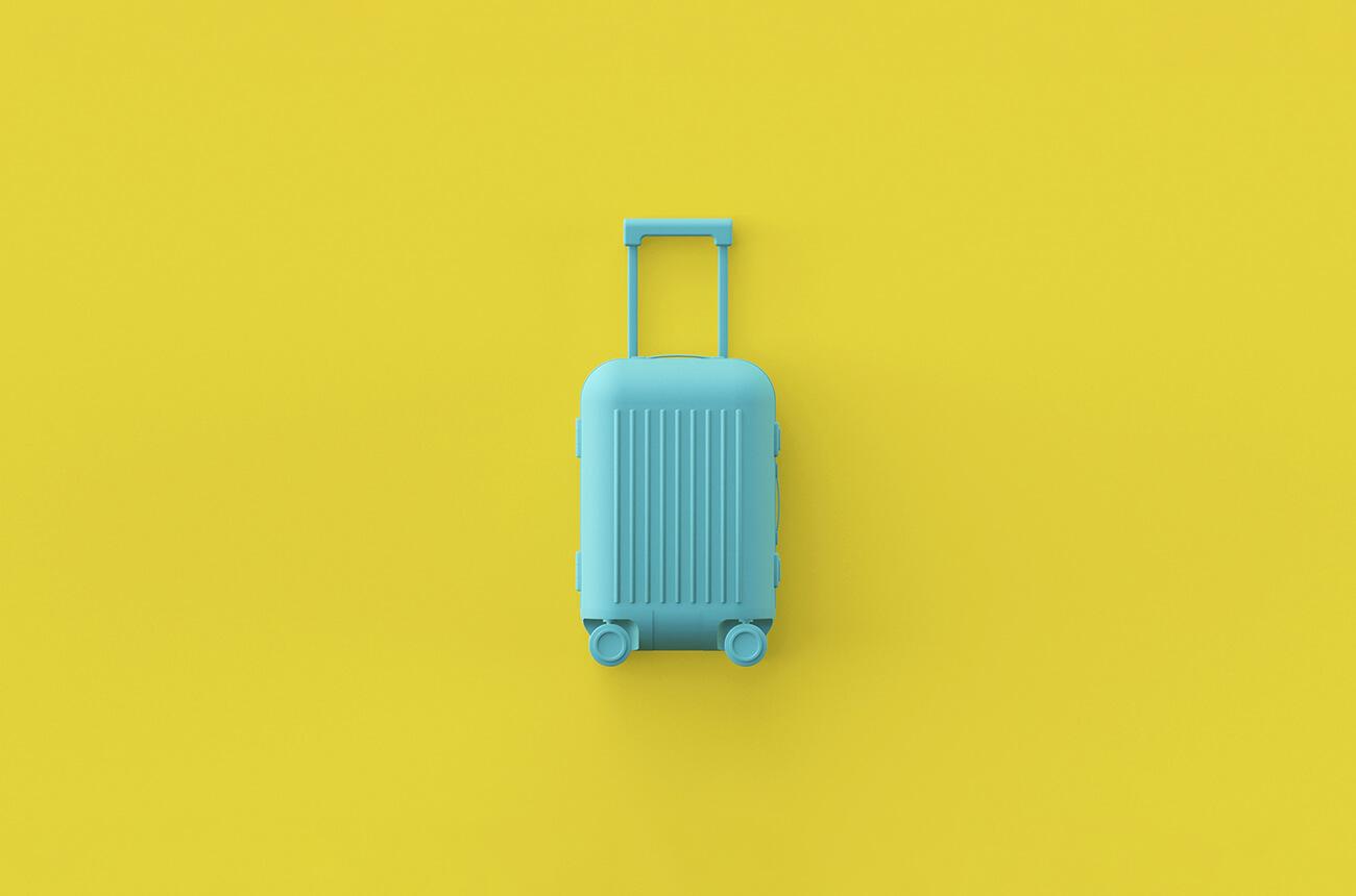 Türkiser Reisekoffer auf gelben Hintergrund.