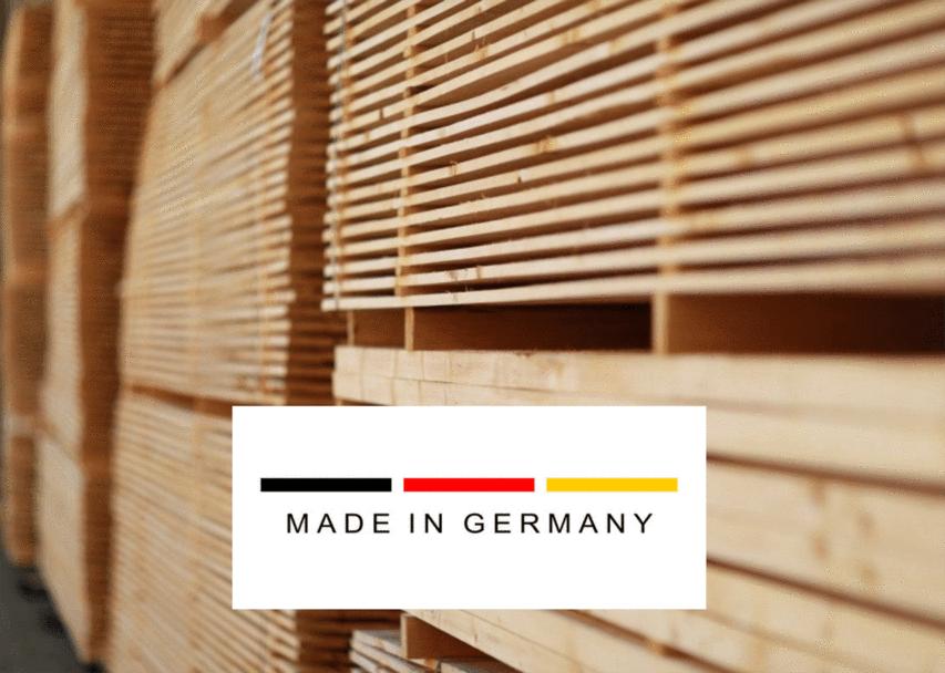 Auf einander gestapelte Holzbretter mit einem Made in Germany Logo für unsere Raum in Raum Systeme.