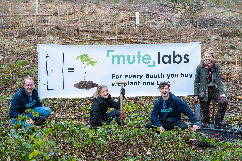 Vier personen stehen im Wald vor einem Plakat mit der Aufschrift One Tree for One Phone Booth