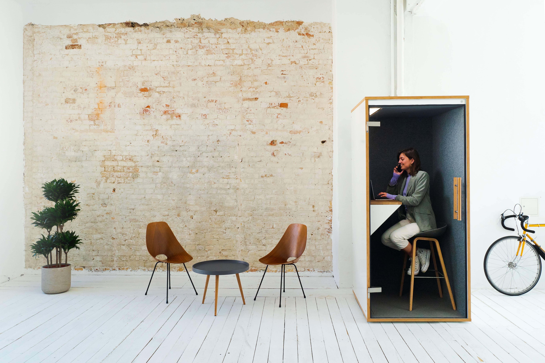 Eine Frau sitzt telefonierend in einer Telefonzelle im Büro. Neben der Telefonkabine ist ein Stuhl mit Tisch und ein Fahrrad.