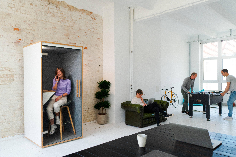 Eine Frau telefoniert ungestört in einer Telefonzelle im Großraumbüro. Zwei Männer spielen Tischfußball.