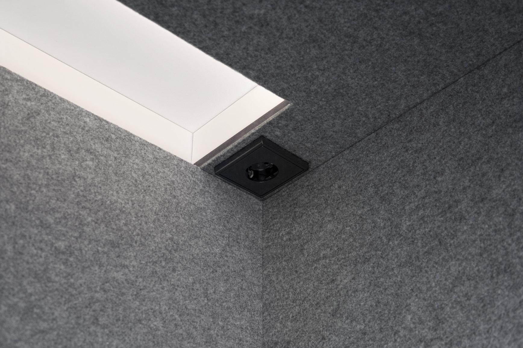 Das Innere, der in grau beschichteten Akustikfilzdecke einer Telefonbox für Büros, mit Steckdose und LED-Beleuchtung.