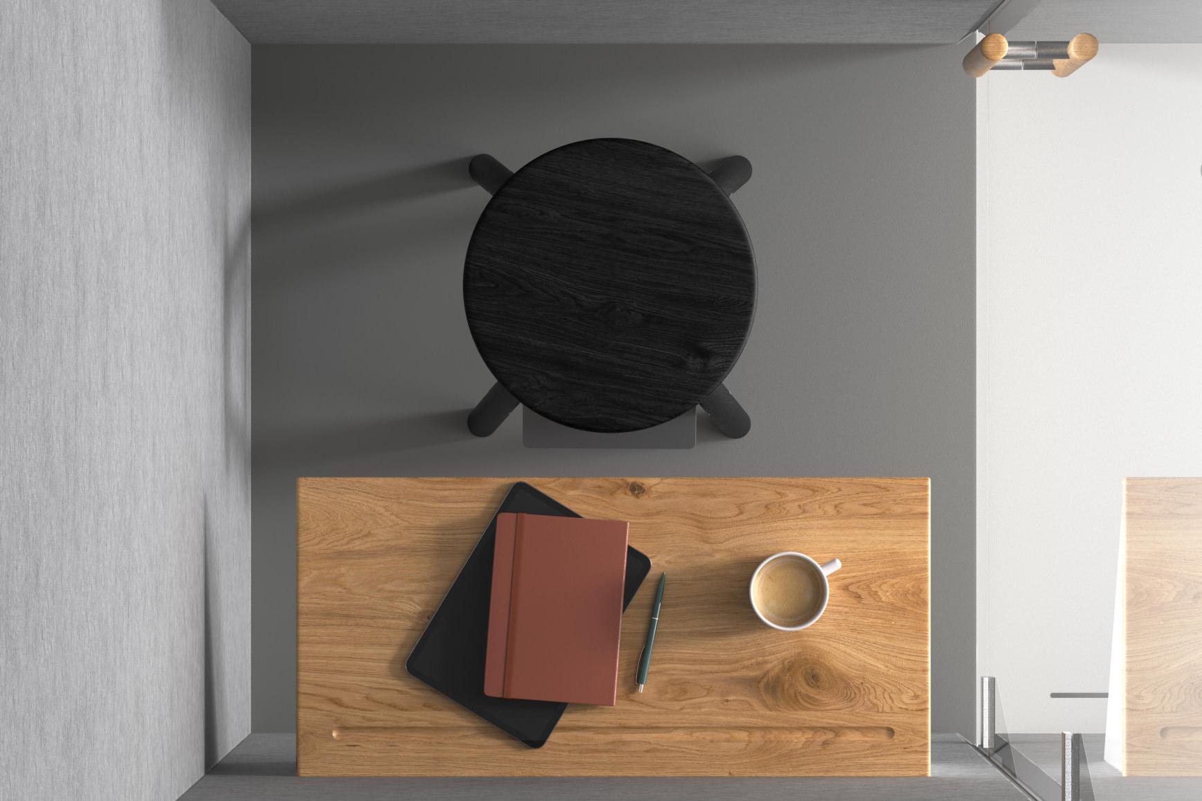 Vogelperspektive in eine Telefonkabine. Man sieht einen Tisch mit Notizbüchern, Kaffeetasse und einen schwarzen Hocker.
