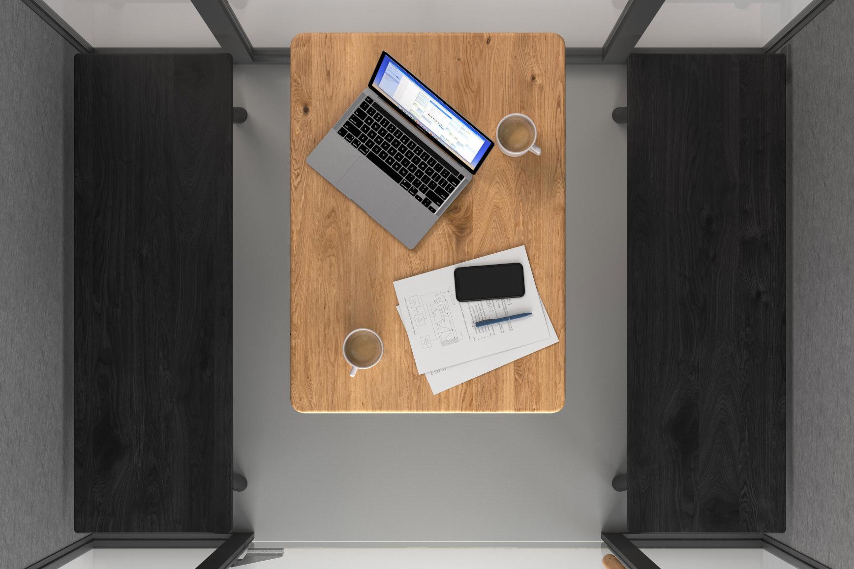 Vogelperspektive in eine Meetingbox. Man sieht einen Tisch mit Notizbüchern, Kaffeetassen und Laptop.