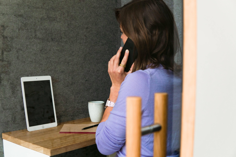 Eine Frau mit lila Pullover telefoniert in einer Telefonbox in einem Büro und starrt auf ein Tablet.