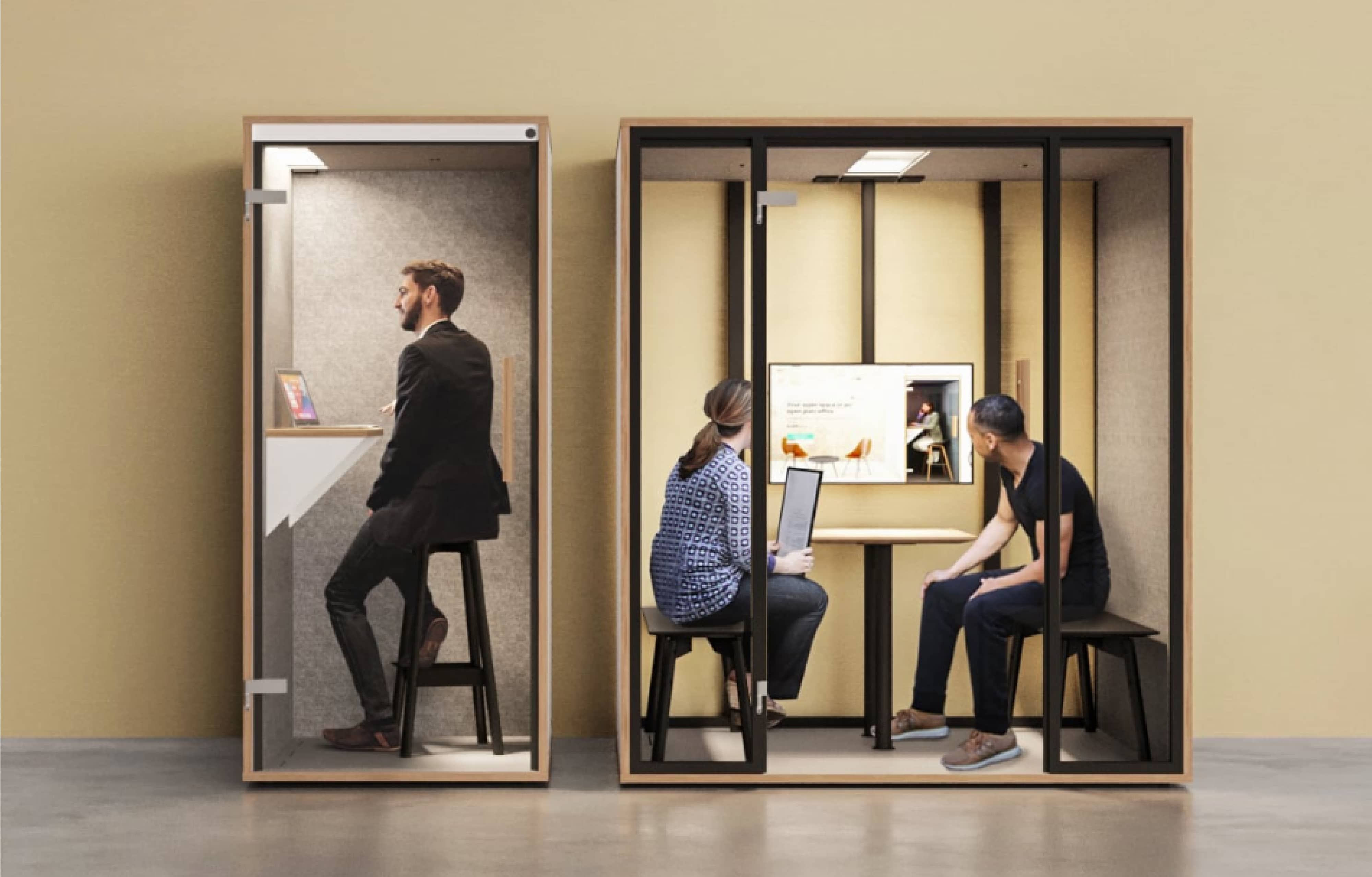 Ein Mitarbeiter sitzt in einer Telefonbox im Büro und telefoniert. Zwei weitere stzen in einer Meetingbox und reden.