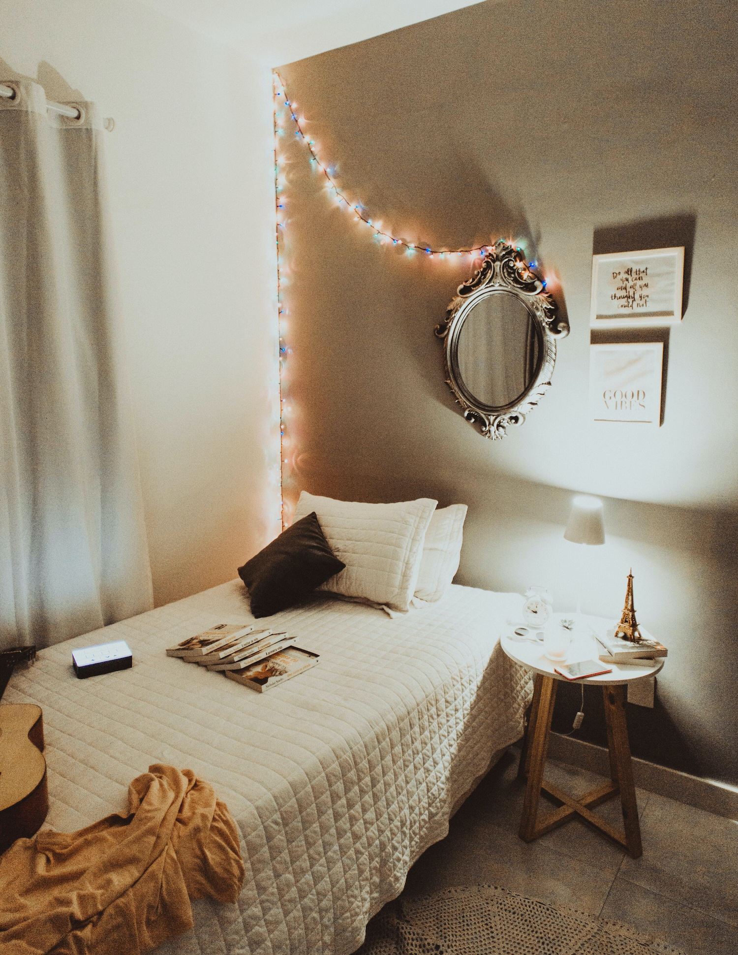 Dorm room with mirror and rainbow string-lights.