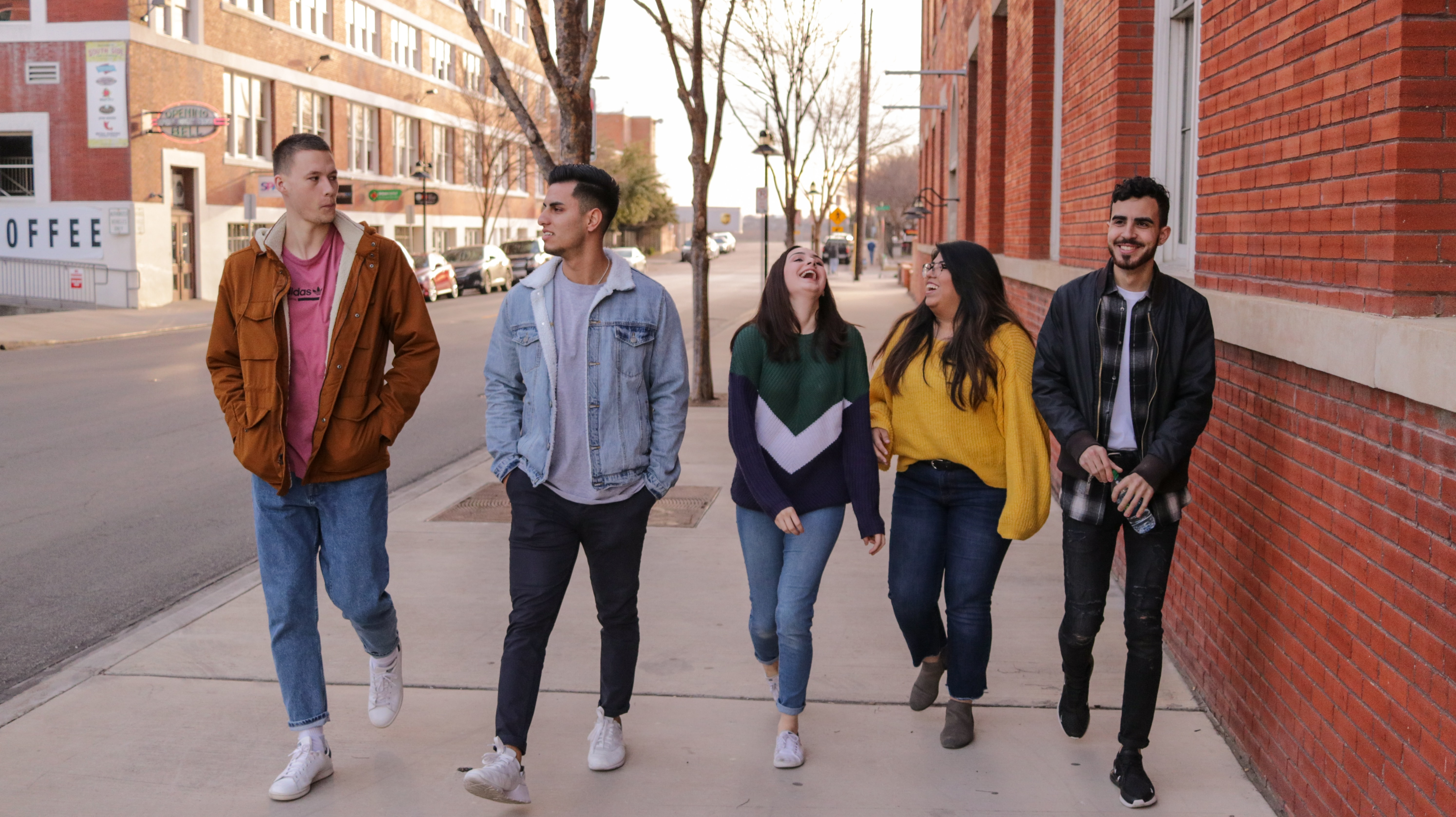 5 college students laughing and talking on the street.