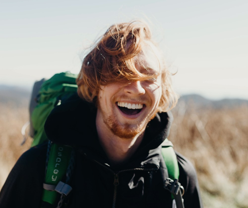 a guy smiling and hiking
