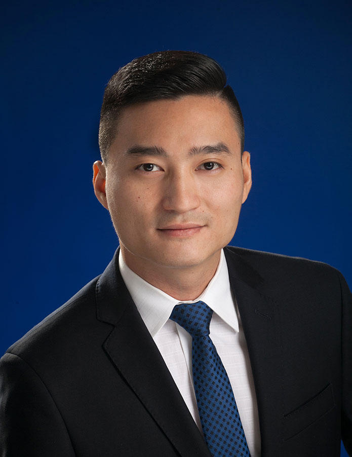 A headshot of Danny Thai with a suit