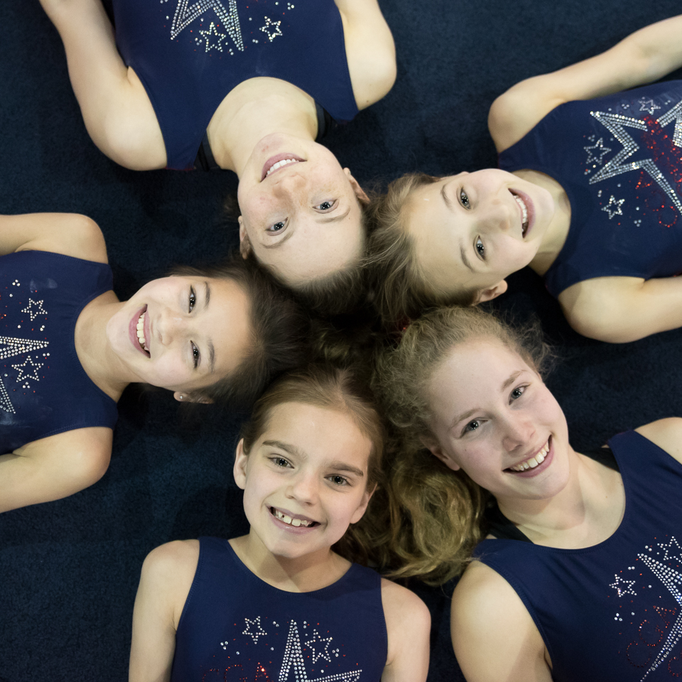 group of smiling gymnasts in a circle on the floor with heads in middle.