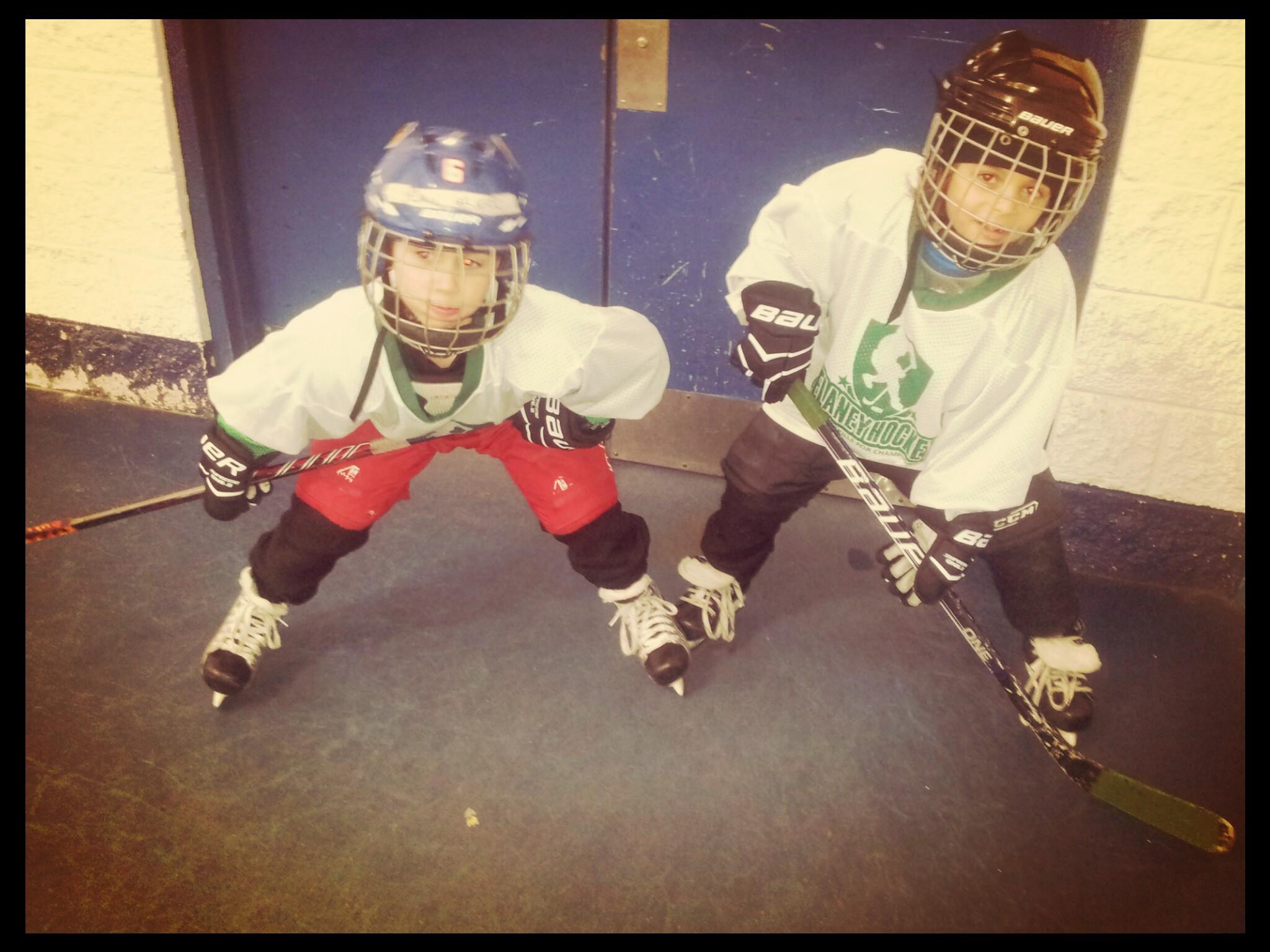 Two small boys in hockey gear.
