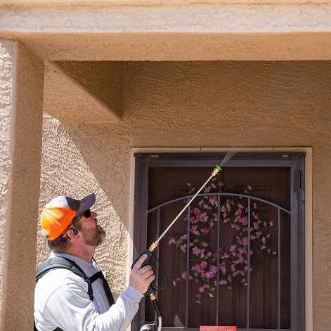 Agro Employee treating for pests outside an Arizona home.