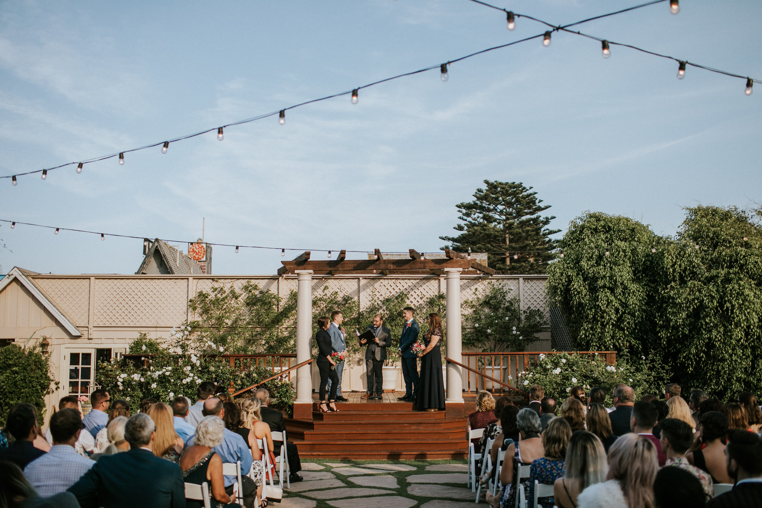 Photo of a wedding, looking down the main aisle at the couple standing on a small stage outdoors