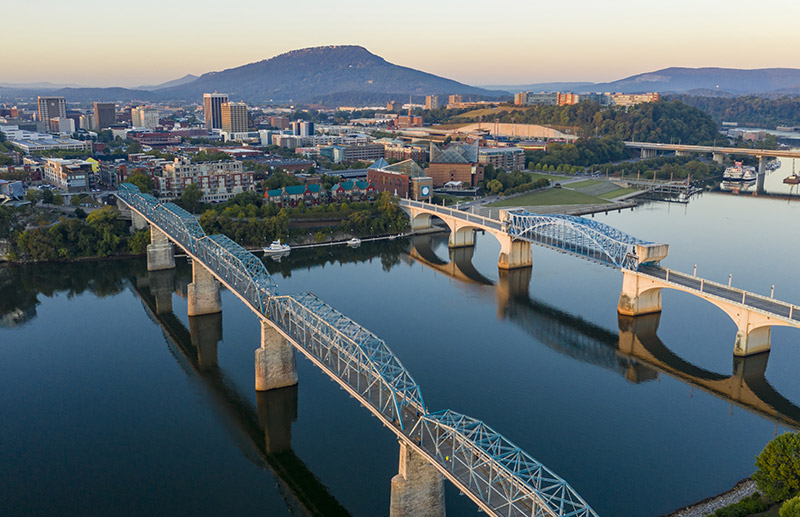 Aerial shot of downtown Chattanooga businesses and parks with Lookout Mountain the background.