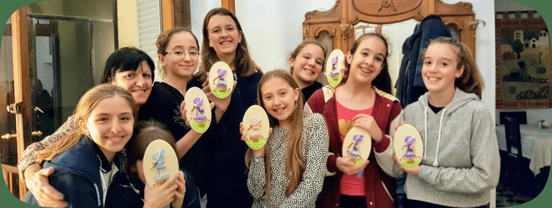 Grupo de chicas sonriendo sosteniendo una artesanía hecha con porcelana fría.