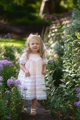A photograph of a young girl in a dress against flowery nature background