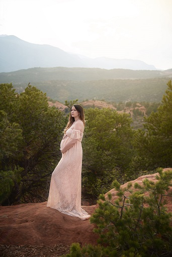 A photograph of a pregnant mother in a dress posing on mountainous terrain