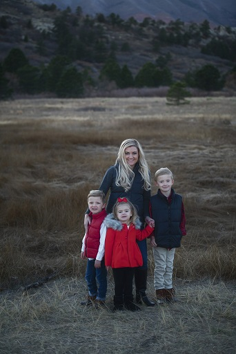 A photograph of a family of four containing a mom and three kids set against nature and mountain background