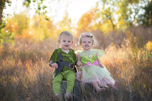 A picture of two children dressed in costumes against forest nature background