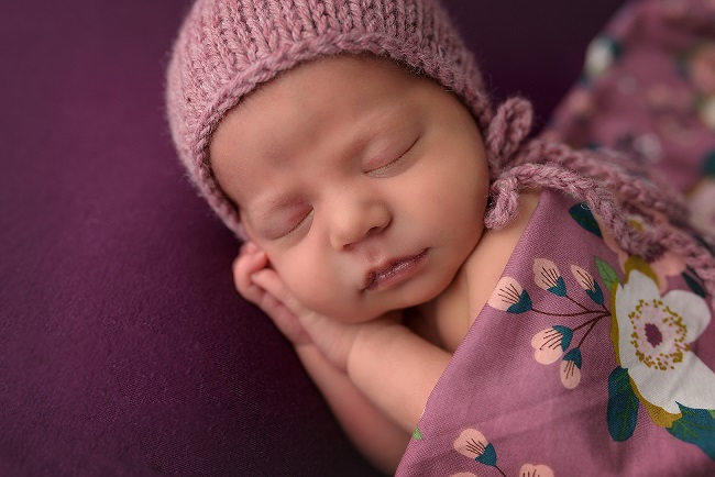 Photograph of a newborn baby girl sleeping and wearing a pink outfit with purple background