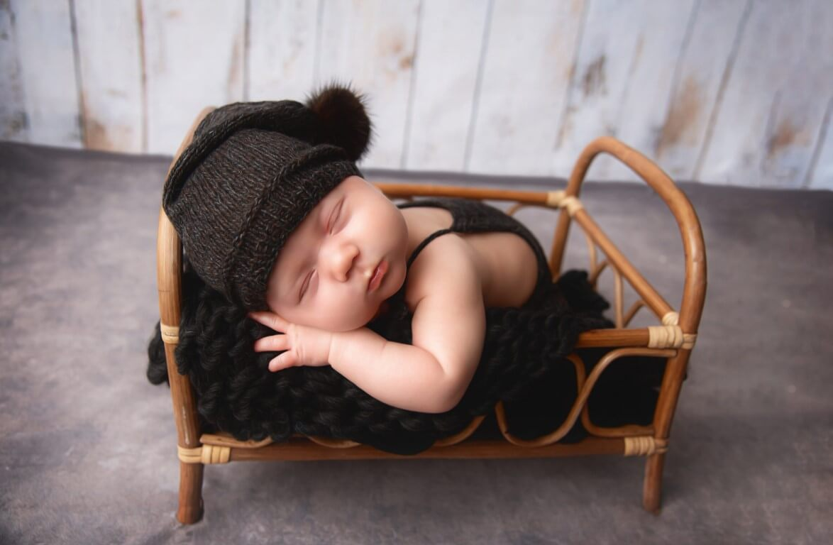 A photograph of a sleeping newborn baby with dark hat on in a small wicker crib