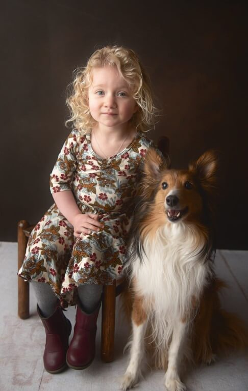 A photograph of a young girl with her dog