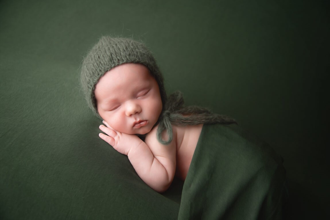 Picture of newborn baby in green outfit with green background