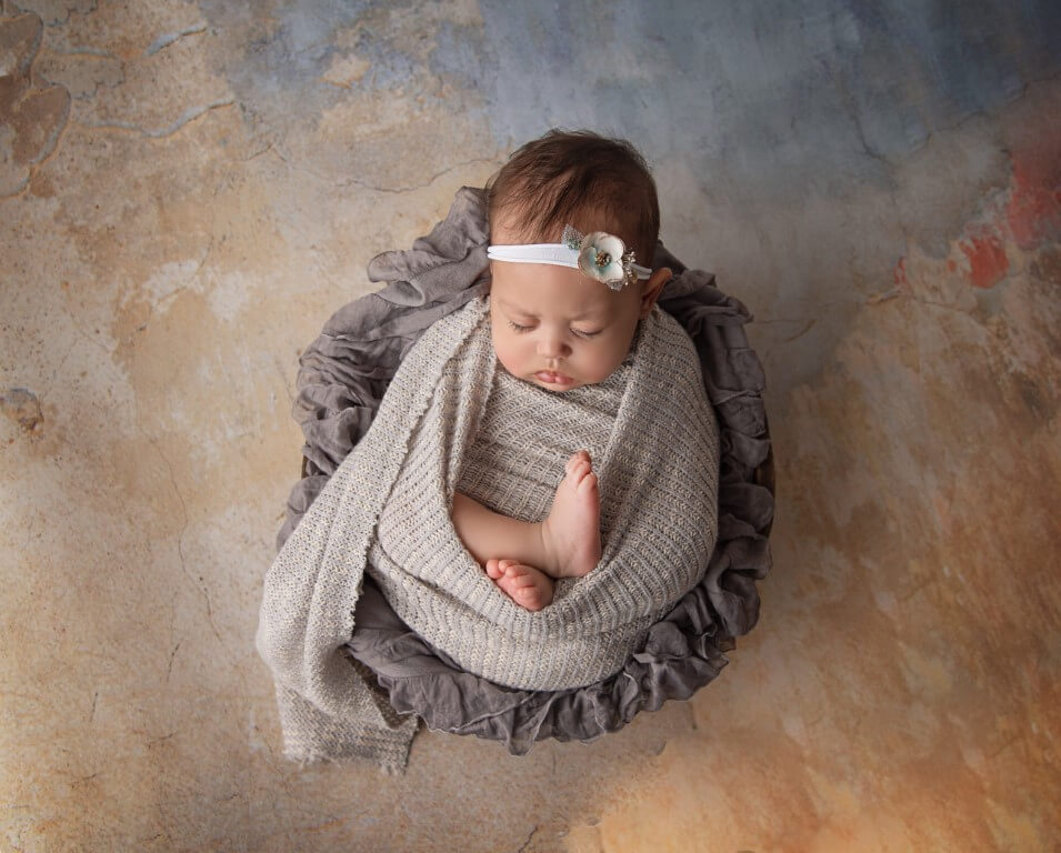 Picture of newborn baby with white flower headband wrapped in tan blanket and sleeping in gray basket