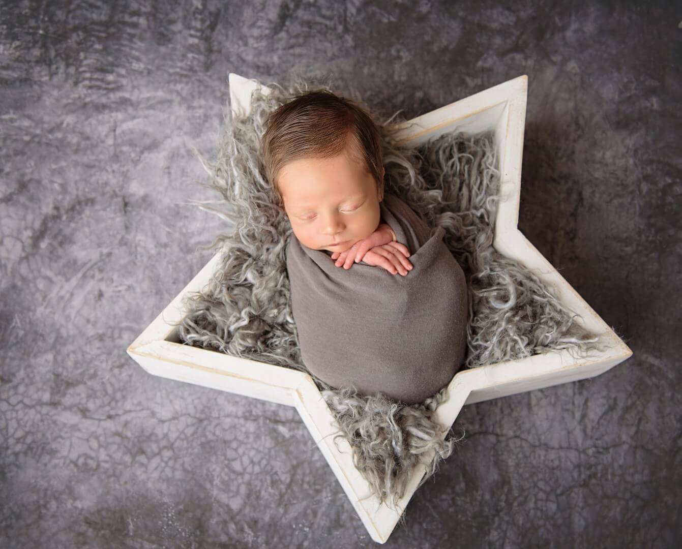 Photograph of a newborn baby in a gray blanket sleeping in a star shaped bed