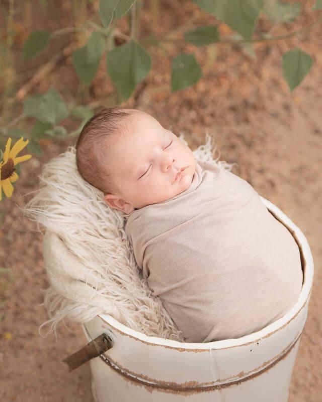 A photograph of a newborn baby sleeping in a bucket
