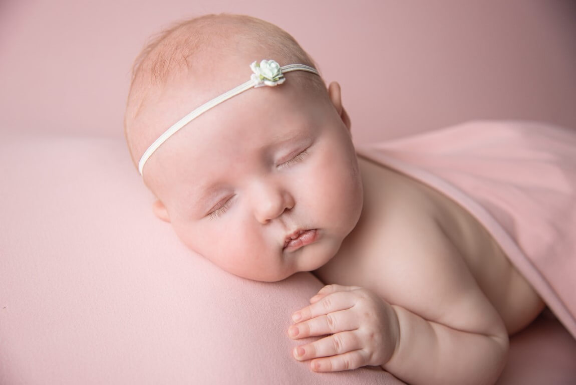 A picture of a newborn baby girl wearing a white flower headband and a pink blanket with pink background