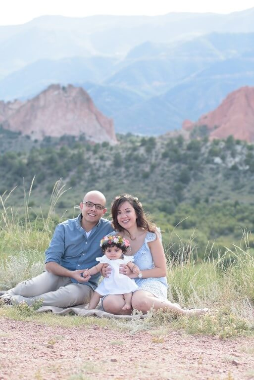 Photograph of family of including baby set against mountain background